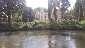 A ruined grand home across the river
